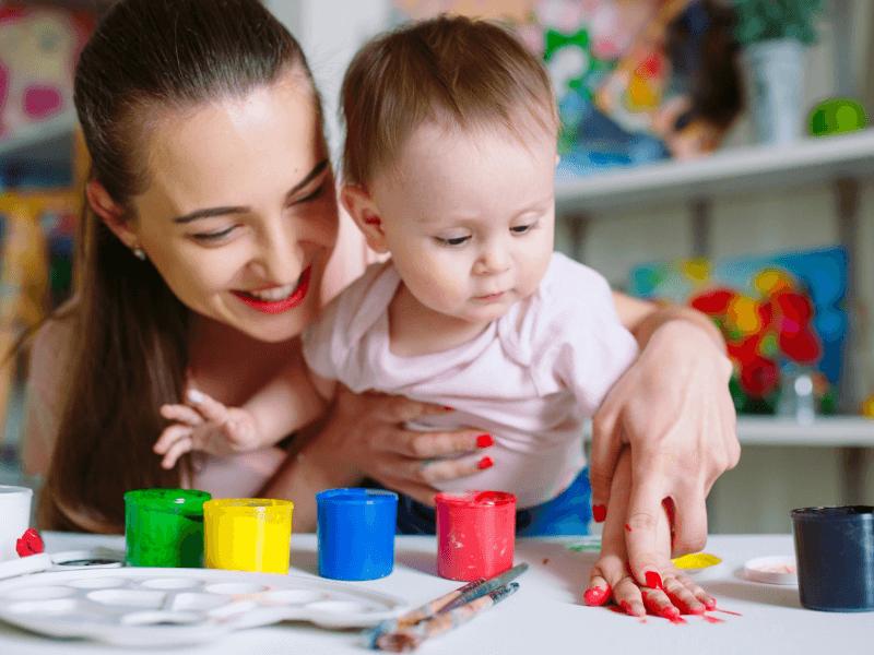 Mamá y bebé felices jugando con pintura